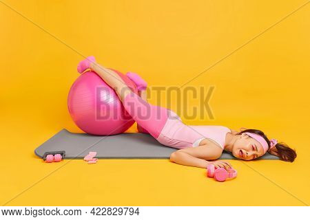 Depressed Exhausted Asian Woman Lies On Fitness Mat After Hard Workout Keeps Legs On Swiss Ball Dres