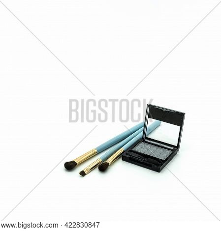 Makeup Accessories. Plastic Box With Gray Eyeshadow. Nearby Are Three Blue Natural Bristle Brushes.