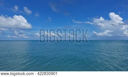 Calm Aquamarine Ocean And Azure Sky With Cumulus Clouds. A Speedboat Is Visible On The Horizon. Sere