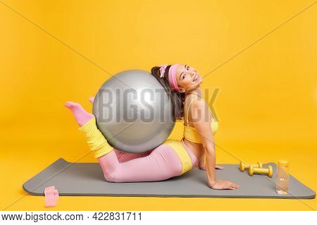 Flexible Slim Woman Has Training At Home Exercises With Swiss Ball Dressed In Activewear Stretches O