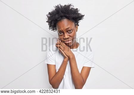 Upset Dejected Dark Skinned Woman Looks With Miserable Expression Keeps Hands Near Face Wants To Cry