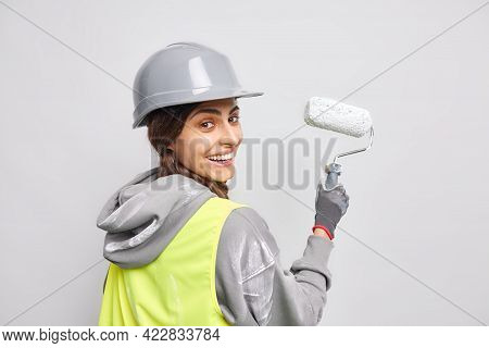 Positive Happy Female Worker In Hardhat And Uniform Paints Wall With Roller Uses Instruments Or Tool