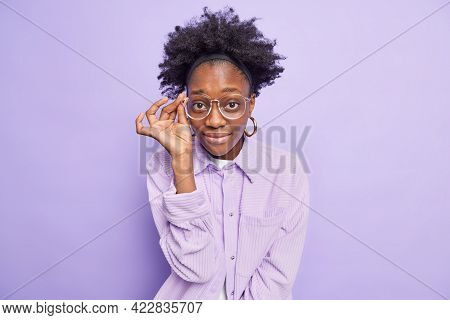 Portrait Of Dark Skinned Woman Looks Attentively Through Spectacles Wears Stylish Jacket Listens Inf