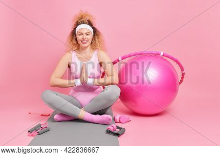 Photo Of Relaxed Woman With Curly Hair Keeps Palms Pressed Together Legs Crossed Practices Yoga Has