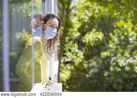 Young Woman In Medical Mask On Window Breathing Fresh Air From Quarantine