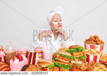 Wrong Lifestyle And Unhealthy Diet Concept. Serious Wrinkled Old Woman Focused Down Looks Attentivel