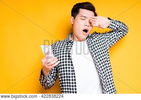 Young Tired Asian Student In Plaid Shirt Holds Phone In Hand And Yawns With Eyes Closed
