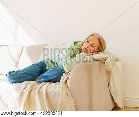 Sad Senior 60s Woman In Casual Clothes Resting On Sofa In Living Room At Home, Feeling Depressed Dur