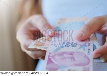 Turkish Lira Banknotes In Woman Hands. The Paper Currency Of Turkey. Current Turkish Liras Are Issue