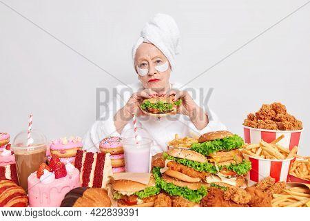 Serious Senior Lady Has Red Lips Eats Hamburger Undergoes Beauty Procedures Looks Directly At Camera