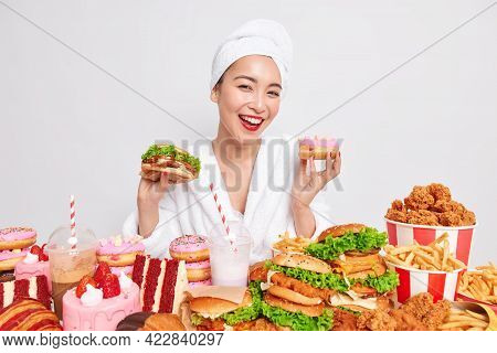 Hungry Asian Lady Smiles Gladfully Holds Doughnut And Sandwich Surrounded By Fast Food Dressed In Ba