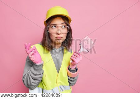 Asian Female Decorator Dressed In Protective Helmet Uniform And Gloves Plans Home Repair Holds Paint