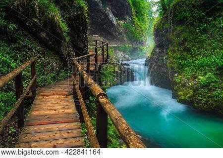 Narrow Wooden Footbridge In The Misty Vintgar Gorge. Beautiful Scenery With Mountain River In The De