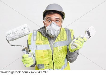 Hesitant Puzzled Male Repairman Shrugs Shoulders Holds Repair Tools Wears Protective Respirator Helm