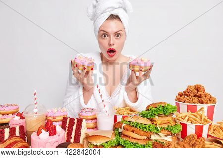 Shocked Hungry Woman Eats High Calorie Fatty Food Holds Two Doughnuts Looks Wondered Expression Wear