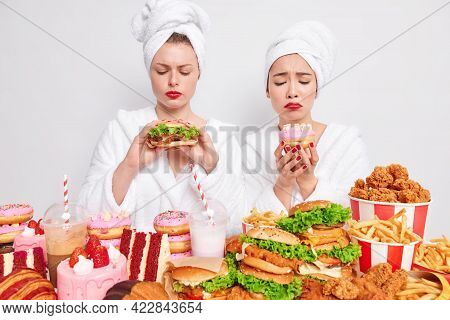 Two Upset Young Women Tempting To Eat Fast Fod Hold Hamburger And Doughnut Have Frustrated Face Expr