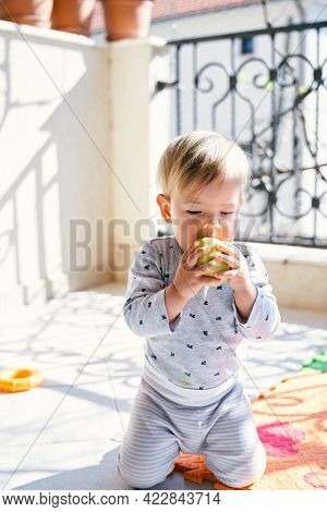 Small Toddler Kneels On A Colored Rug On The Balcony And Gnaws An Apple