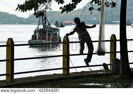 Sandakan. Malaysia. November 27, 2018. A Fisherman From The Village Of Sea Gypsies Repairs A Fishing