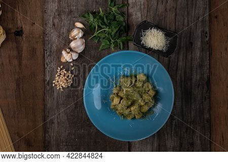 Top view of homemade gnocchi with pesto sauce, parmesan and basil isolated on wooden table