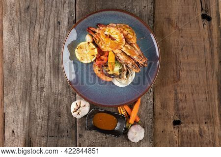 Top view of wok-fried prawns with garlic and chili isolated on wooden rustic table