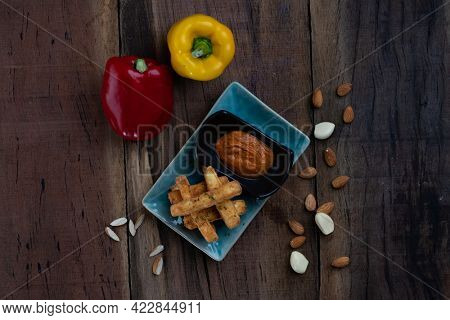 Deep-fried haloumi cheese with panko crust and romesco sauce isolated on rustic wooden table