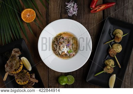Top view variety set of main courses, seafood and meat isolated on rustic wooden table