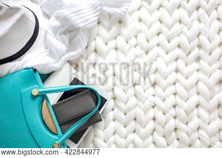 Top View Neatly Storage Necessary Things Of Female Handbag Organizing On White Knitted Plaid