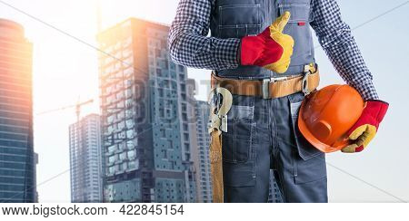 Electrician In Uniform Showing Thumb Up  At Construction Site. Banner.