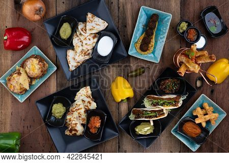 Top view variety of delicious starters from around the world isolated on rustic wooden table
