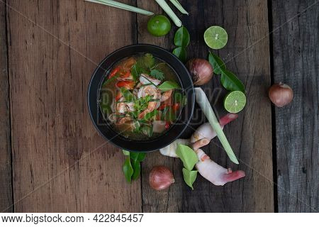 Top view of traditional spicy prawn soup with galangal, lemongrass, kaffir lime leaf and straw mushrooms isolated on the wooden table