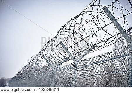 Prison Fence. Grid Fence With Barbed Wire Against Sunset. Barbed Wire. Security Measures For Prisone