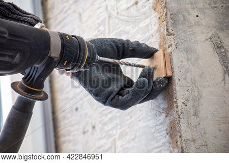 Male Hands Of  Construction Worker Drills  Hole In Concrete With  Hand Drill. The Process Of Drillin