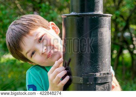 8-year-old Boy With Dark Hair Stands Behind A Metal Lamppost. Cute Brunet Boy Playing Hide And Seek