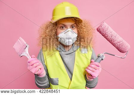 Busy Curly Haired Woman Decorator Wears Protective Respirator And Hardhat Holds Painting Tools Ready