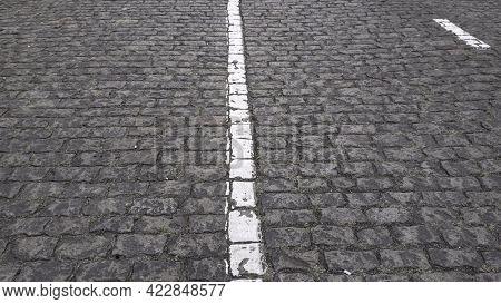 Ancient Stone Paving Road In Old Town. Cobblestone Pavement With Damaged White Single Line Road Mark