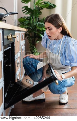 Astonished Young Adult Woman In Apron Looking Into Oven With Open Mouth In Modern Kitchen