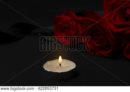Burning Mourning Candle And Red Roses With Black Mourning Ribbon On A Dark Background. The Concept O