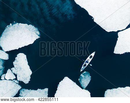 Kayak Sailing Between Ice Floes On Baikal Lake In Spring. Aerial Drone View. Baikal Lake, Siberia, R