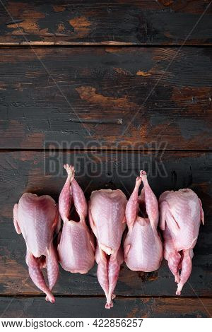 Raw Uncooked Quails Set, Top View, On Dark Wooden Background  With Copy Space