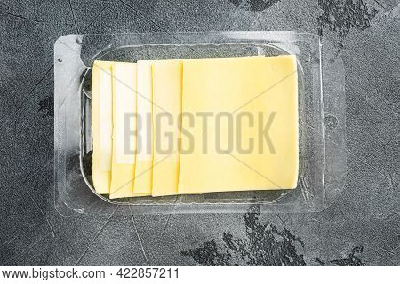Yellow Cheese Slices Of Cheddar Set, In Plastic Pack, On Gray Stone Background, Top View Flat Lay