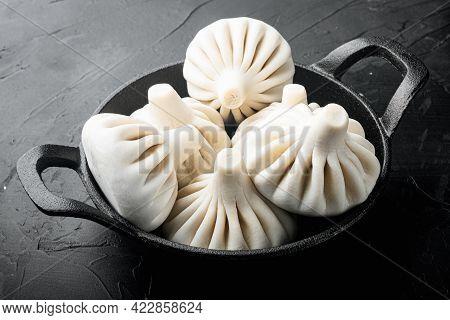 Uncooked Baozi Chinese Dumplings. Azian Dumplings Set, In Frying Cast Iron Pan, On Black Stone Backg
