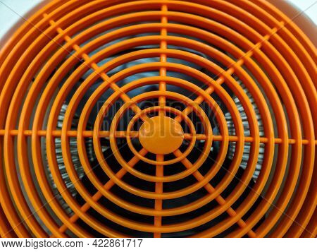 Household Fan With Orange Protective Grill. Close-up. Selective Focus.