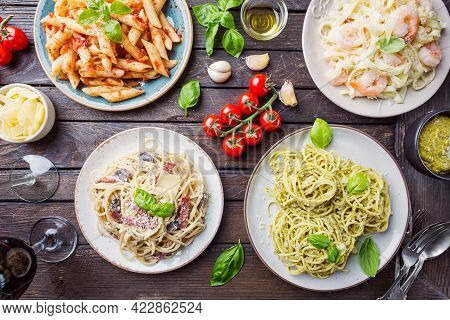 Several Plates Of Pasta With Different Kinds Of Sauce Over Wooden Background, Top View. Concepts Of