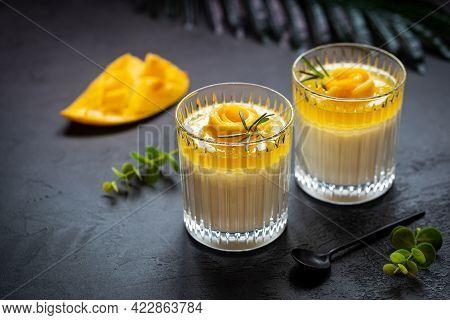 Italian Dessert Panna Cotta With Mango In Glass Over Dark Background