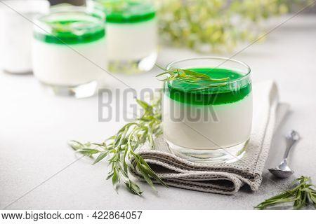 Dessert Panna Cotta With Green Tarragon Sauce And Fresh Tarragon On White Background
