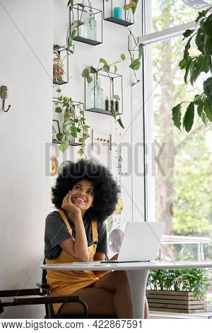 Young Thoughtful Dreamy Smiling African American Student Generation Z Girl With Afro Hair Sitting At