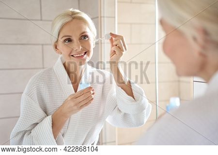 Senior Mature Older Caucasian Woman Touching Clean Face Eye Contour With Antiaging Pipette Serum Ess