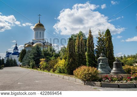 Ancient Bronze Bells & Trinity Cathedral With Gold Domes On Background. Photo Taken In Zilantov Fema