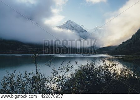 Beautiful View Through Branches Silhouettes To Mountain Lake And Snow-capped Mountains Above Thick C