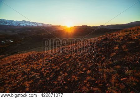 Awesome Autumn Landscape With Hills And Great Snow-covered Mountain Range In Golden Sun Rays. Specta